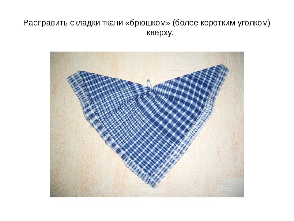 Расправить складки ткани «брюшком» (более коротким уголком) кверху.